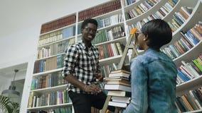 Nedersta sikt av den afrikanska grabben som väljer böcker från hyllorna, medan stå på stege och ge böcker till den afrikanska fli arkivfilmer