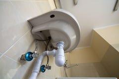 Nedersta sikt av den nya vita handfatvasken f?rbindelse f?r att f?rse med kloaker p? bakgrund av beigea keramiska tegelplattor f? royaltyfria foton