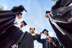 nedersta sikt av lyckliga unga graderade studenter framme av royaltyfria bilder