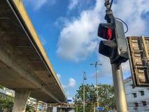 Nedersta sikt av röd trafikljus för gångare på genomskärningen på bakgrund för blå himmel för moln arkivbild