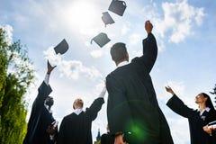 nedersta sikt av unga graderade studenter som upp framme kastar hattar av arkivfoto