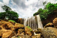 Nedersta sikt av vattenfallet bland gröna trän SOMMAREN landskap Royaltyfri Fotografi
