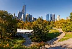 Nedgång i Central Park: Wollman isbana- och Manhattan highrises Arkivbilder
