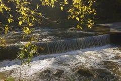 Nedgångfärger över en avskild vattenfall Royaltyfria Bilder