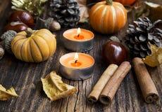 Nedgånggarnering Pumpor, orange stearinljus, kanel, kastanjer och A Arkivfoto