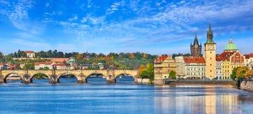 Nedgånglandskapsikt till den Charles bron på den Vltava floden i den Prague Tjeckien med blå himmel och med moln Royaltyfria Bilder