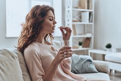 Need another antibiotic. Sick young woman taking pills while sitting on the sofa at home stock photo