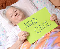 Need care. Old woman holding need care blank Stock Image