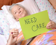 Need care. Old woman holding need care blank stock images