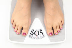 Need diet. Womans feet on bathroom scale Royalty Free Stock Photography
