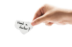 Need a doctor?. Need a doctor question concept using a hand holding a piece of paper and the text written by hand with a permanent marker Royalty Free Stock Image
