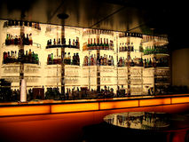 Need a Drink?. Bar Counter with bottles of alcohol and glasses on display Stock Images