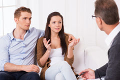 They need an expert advice. Frustrated young couple telling about their relationship problems to psychiatrist Royalty Free Stock Image