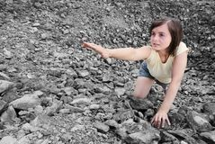 Need a help. Young woman needs help and stretches her hand from rocky hole Royalty Free Stock Photo