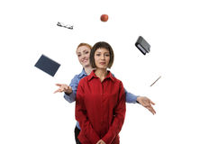 Need a helping hand. Woman standing behind another women helping her to juggle objects Stock Photos