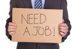 Need a job. Businessman holding a cardboard sign looking for a job Royalty Free Stock Photos