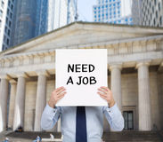 Need a job. Businessman holding placard with need a job Royalty Free Stock Image
