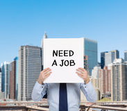 Need a job. Businessman holding placard with need a job Stock Image