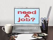 Need a job. Notebook with stationery and need a job on screen Royalty Free Stock Image
