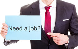 Need a job. Smart young businessman in dark suit, white shirt and red tie holding sheet with text 'Need a job ?' pointing finger at it and indicating that he is Royalty Free Stock Image