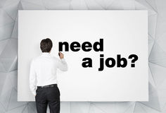 Need a job. Young businessman drawing need a job on placard Royalty Free Stock Photography