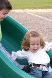 Need A Little Help?. Smiling little girl being helped along on a sliding board by her brother's foot on her hip Stock Photo