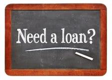 Need a loan? Blackboard sign. White chalk text on a vintage slate blackboard stock photography