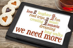 We need more love and dreams. Word cloud on a digital tanlet with tea and heart cookies - what we need more: love, dreaming, music, tea, creations, long walks Stock Photography