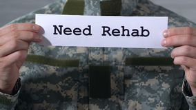 Need rehab written on paper in hands of male soldier, help to war veterans