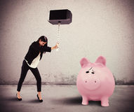 Need savings. Woman breaks with a hammer a piggybank Royalty Free Stock Image