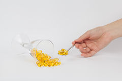 Need some fish oil?. Reclining glass and a spoon of fish oil Stock Photos