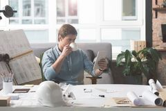 Skillful youthful architect enjoying fresh espresso. Need some pause. Pleasant young engineer is drinking coffee and reading news on tablet while resting in Royalty Free Stock Photos
