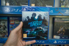 Need for Speed. Bratislava, Slovakia, circa april 2017: Man holding Need for Speed videogame on Sony Playstation 4 console in store Royalty Free Stock Images