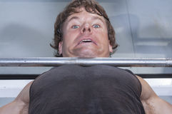 Need a spot. Closeup of helpless expression of Caucasian man stuck under heavy barbell on bench press at gym royalty free stock photos