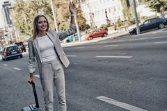 Need a taxi. Beautiful young woman in suit hailing a ride and smiling while standing outdoors royalty free stock image