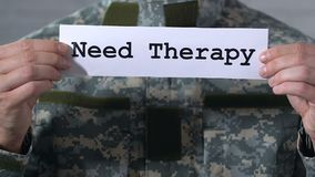 Need therapy written on paper in hands of soldier, PTSD treatment, closeup. Stock footage stock video footage