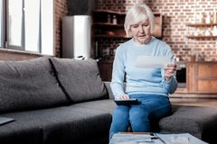 Attentive senior female calculating her savings royalty free stock image