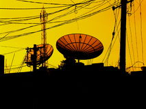 A need to Communicate. Several satellite dishes and cellphone tower amoung cables run between poles Stock Images