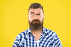 Need to think. Man serious face raising eyebrow not confident. Have some doubts. Hipster bearded face not sure in. Something. Doubtful bearded man on yellow stock photos