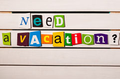 Need a vacation - written with color magazine letter clippings on wooden board Stock Images