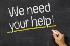 We need your help. Blackboard with the text We need your help Stock Image