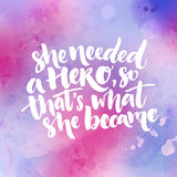 She needed a hero, so that`s what she became. Inspirational feminism quote about woman. Typography at purple and pink. Watercolor texture Stock Image