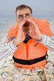 Needing help. Image of troubled man wearing life vest crying for help with dollar bills around him Royalty Free Stock Images