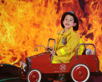 Needing Help Over Here!. A preschool fireman calling for reinforcements for the huge blaze behind his vintage toy fire truck Stock Photo