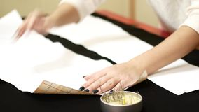 Needle bed with safety pins. Woman seamstress pulls the safety pin of the needle bed. Tools and accessories for sewing