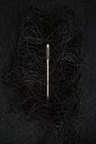 Needle and black thread on black background. Vertical needle and black thread on black background Stock Photos