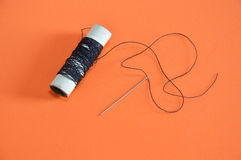 Needle and black thread spool Royalty Free Stock Photography