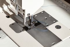 Needle with blue thread and steel presser foot. Of industrial sewing machine close up stock photo
