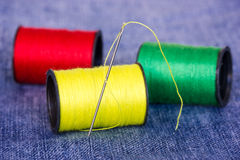 Needle with bobbins on jeans material Stock Image