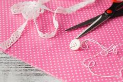 Needle and button on pink polka dot cloth Stock Image